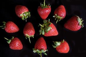 jordgubbfruktmönster på svart bakgrund foto