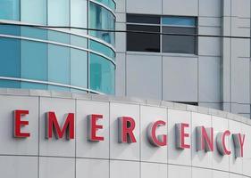 närbild av röda akutskylt på sjukhusbyggnad foto