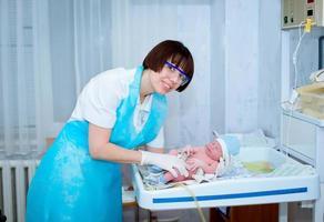 glad läkare med ett barn i armarna foto