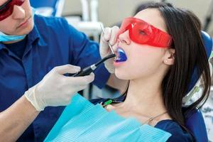 tandbehandling. tandläkare som håller en ultraviolett lampa i mou foto
