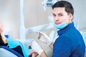porträtt av en tandläkare på jobbet. säker tandläkarkontroller foto