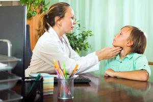 läkare kontrollerar sköldkörteln av tonåring foto