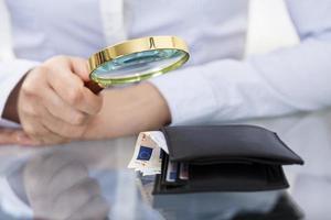 affärsperson med förstoringsglas och plånbok foto
