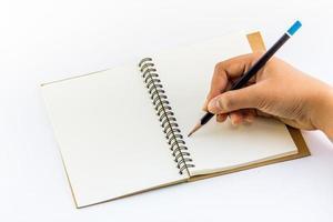 hand skriva på anteckningsboken foto