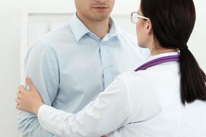 vänlig kvinnlig läkare vidrör manlig patients arm för empati foto