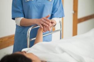 patient som ligger på en medicinsk säng som håller handen
