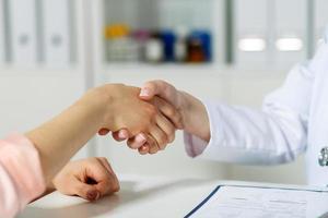 läkare skakar hand med patienten foto