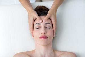 fysioterapeut som gör huvudmassage foto