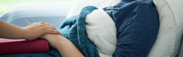 kvinna som ligger i sängen och handhålls av en annan person foto