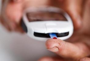 händerna på äldre diabetiker kvinna mäter blodsocker med portabl foto