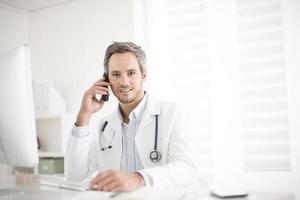 ung läkare på telefon på sitt kontor foto