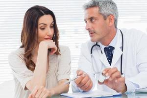 allvarlig läkare lyssnar på sin patient foto