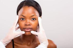 läkare gör hudkontroll på afrikansk kvinna foto