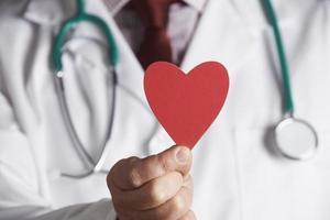 närbild av läkare som håller kartonghjärta foto