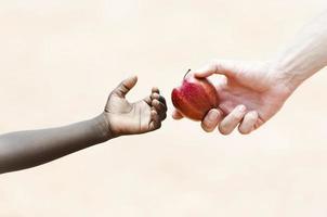 hälsosymbol: ge äpplen för att hjälpa svarta afrikanska etnicitet barn foto
