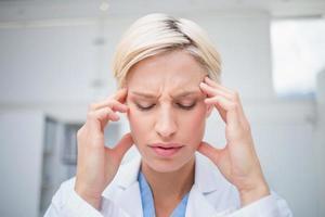 läkare som lider av huvudvärk foto