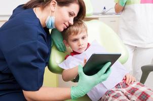 modern tandläkare använder den trådlösa surfplattan med barnpatient foto