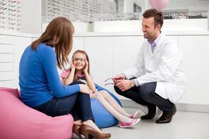 mamma som besöker optiker, optiker med barn foto