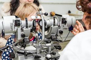 optiker med patient, som ger en ögonundersökning foto