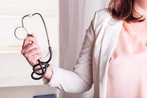 läkares hand som håller ett stetoskop foto