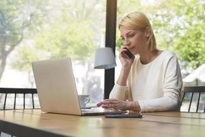 säker kvinna talar i mobiltelefon när man sitter vid bordet foto