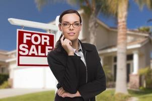 ung kvinna framför huset och försäljning tecken foto