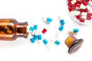 blå kapslar och röda kapslar med flaska, sjukvård och medicin foto