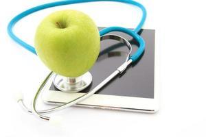 medicinskt stetoskop och äpple på isolerad tablett foto