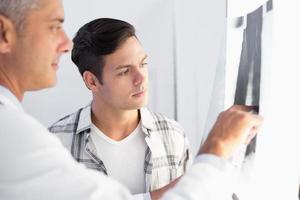 läkare som visar röntgenstrålar till sin patient foto