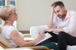 deprimerad affärsman med psykoanalytiker foto