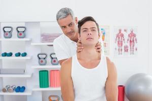 läkare massera en ung man hals foto