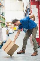 arbetare med ryggvärk medan du lyfter lådan i lager foto