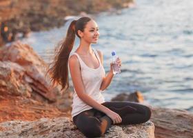 porträtt halv ansikte av ung kvinna dricka vatten foto