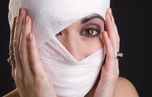 kvinna extrem smärta händer som håller huvudet lindad första hjälpen foto