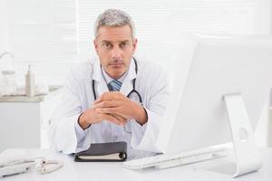 unsmiling läkare tittar på kameran foto