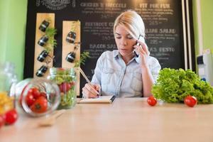 ägaren till den lilla restaurangen skriver order på papper foto