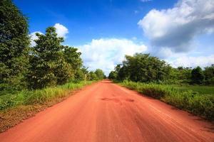 röd grusväg i den tropiska djungeln foto