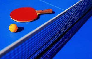 bordtennisutrustning racket, boll och nät foto