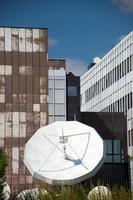 kommunikationssatellit med företagsbyggnadsbakgrund foto