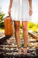 flicka med retro resväska på järnväg foto