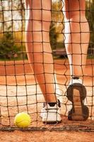 tennis koncept med boll, nät och kvinnor ben foto