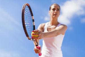 ung kvinna som spelar tennis foto