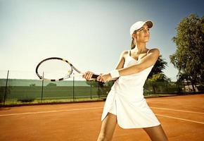 kvinna spelar tennis foto