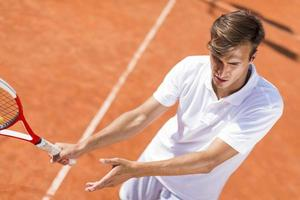 ung man spelar tennis foto