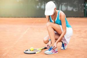 tennisspelare som knyter skosnören foto