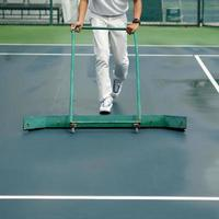 rengöringspersonal som torkar tennisbana efter regn