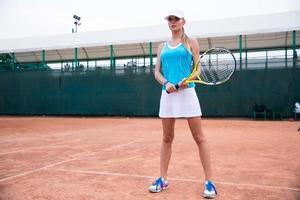tennisspelare som står med racket utomhus foto