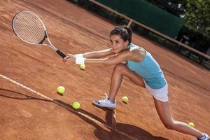 ung flicka som spelar tennis på banan foto
