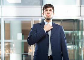 affärsman som justerar sitt slips foto