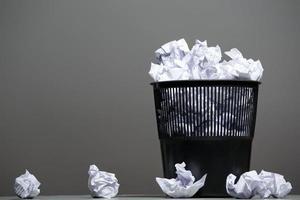 papperskorg fylld med skrynkliga papper foto